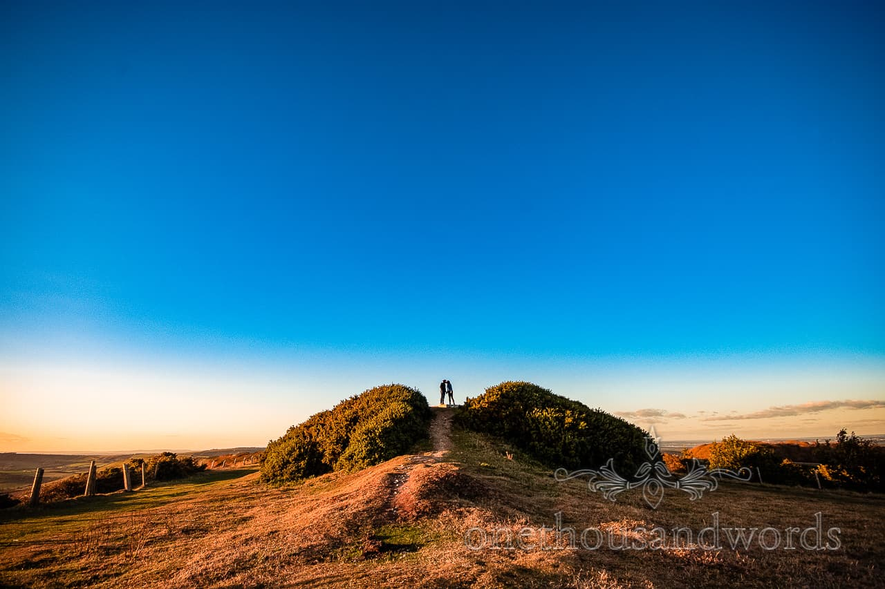 Couple kiss standing on top of hill in Swyre head in Dorset