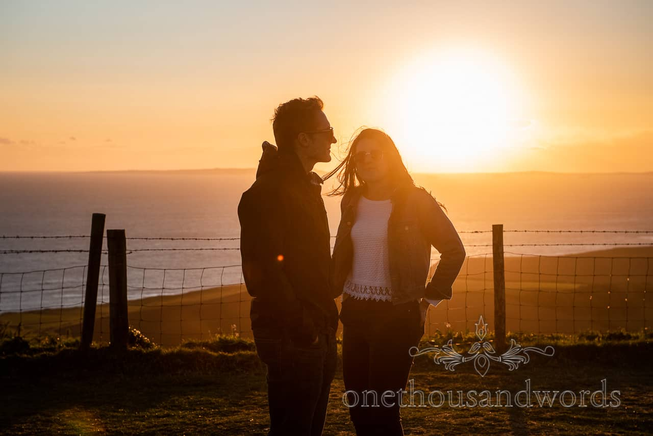 Dorset coast engagement shoot couple in sunglasses with sunset over sea