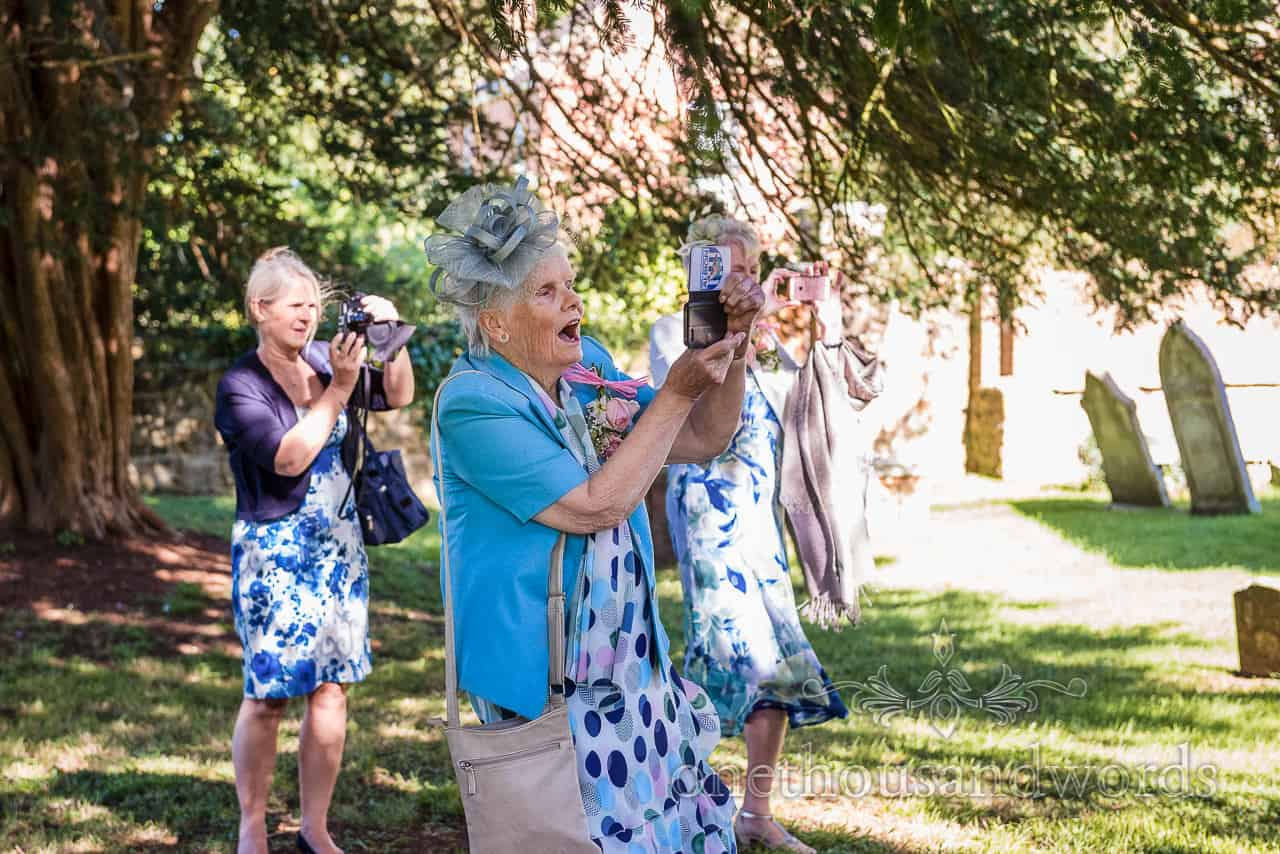 Elderly wedding guests in blue printed dresses take photographs outside the church