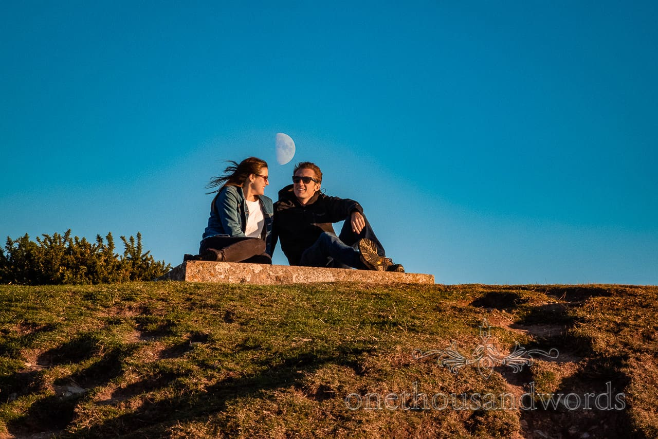 Engagement photoshoot couple sit on Swyre Head hill with moon in the sky