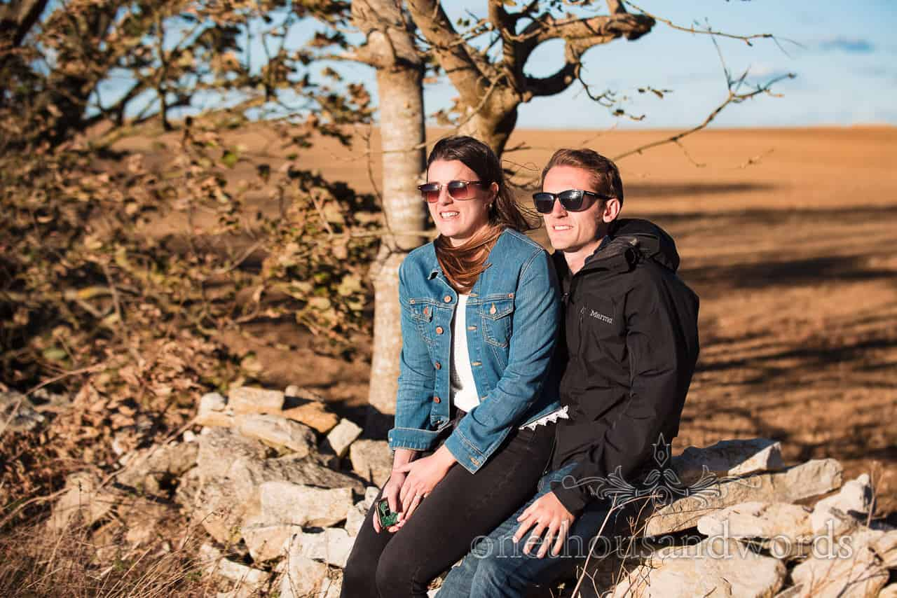 Swyre Head engagement photographs sit on dry stone wall in Dorset