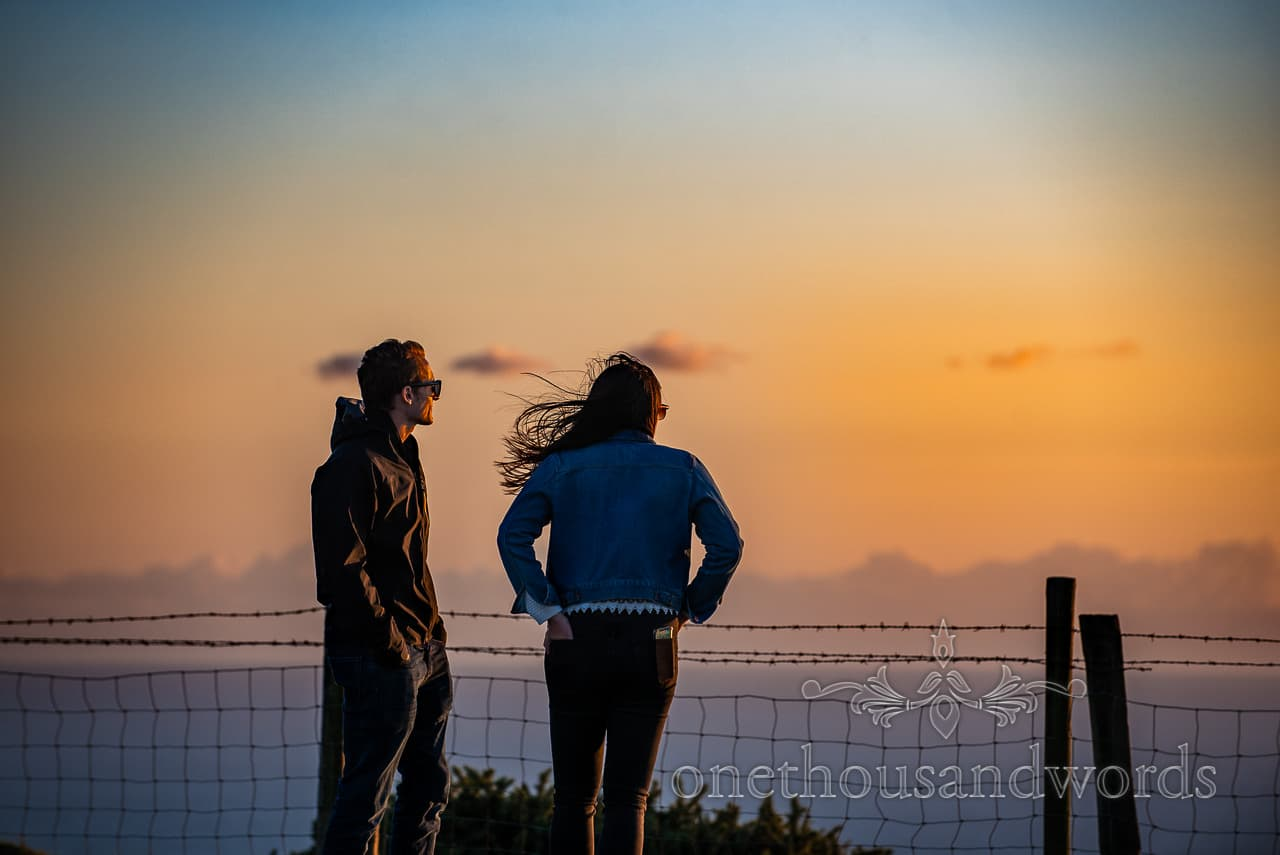 Engagement photo shoot couple watch sky change colour at sunset