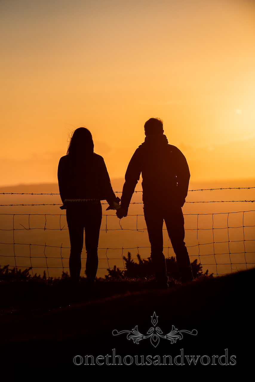 Silhouetted couple stand hand in hand watching sunset over the sea