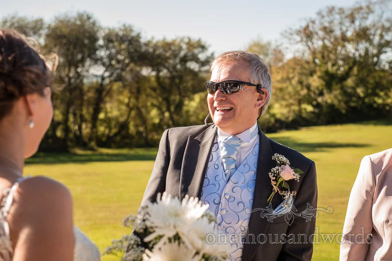 Father of the bride in sunglasses laughing in the sun at countryside drinks reception