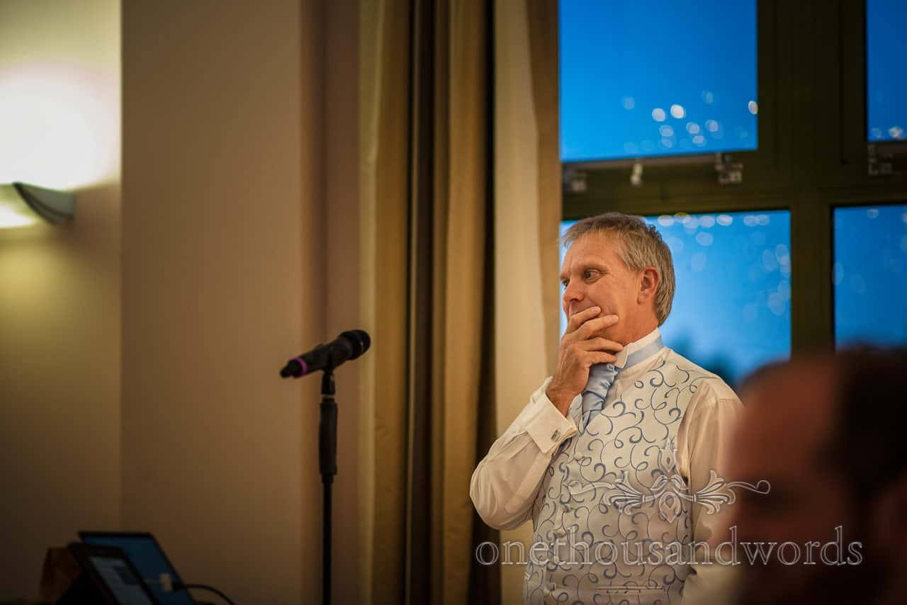Father of the bride listens to answers at wedding quiz