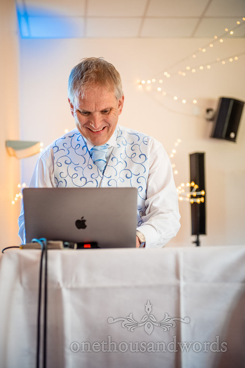 Father of the bride DJing a wedding on his Apple laptop