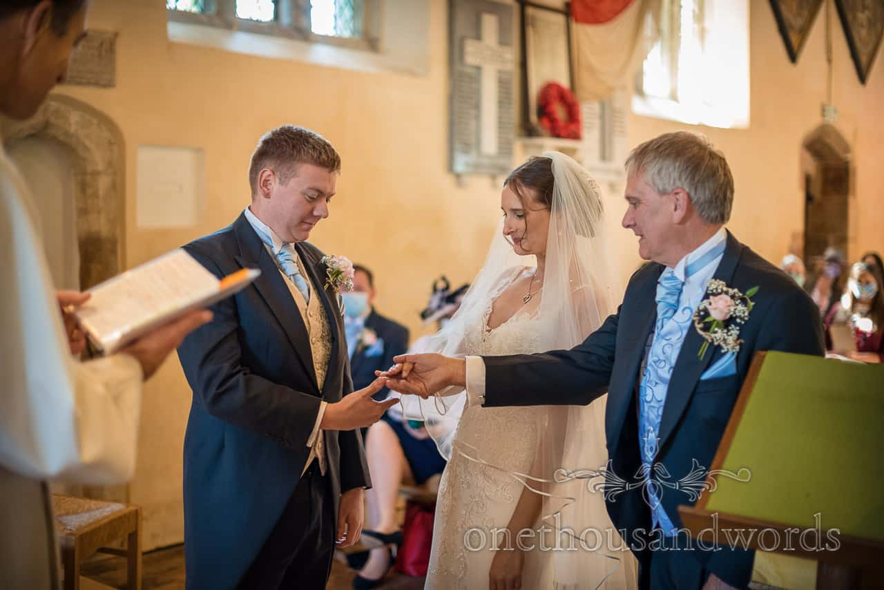Father gives bride's hand to groom during church wedding ceremony