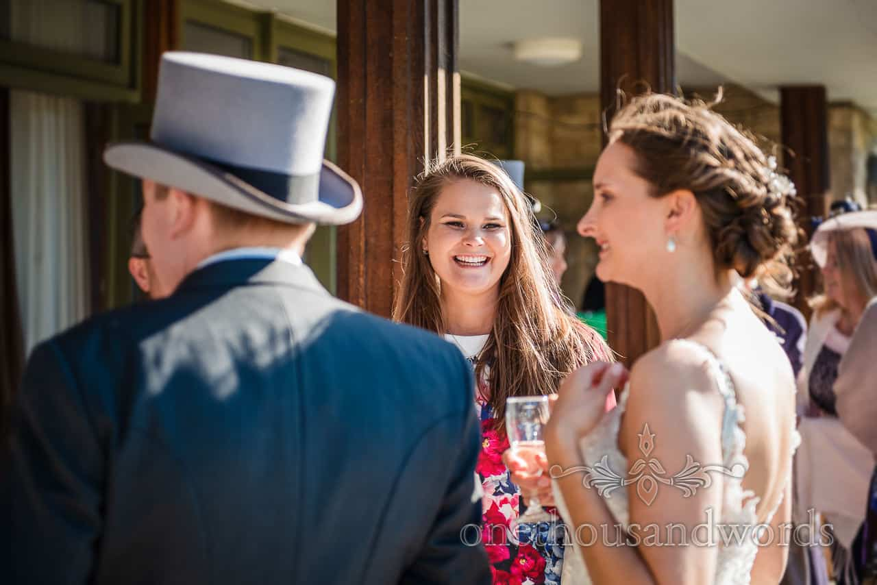Female wedding guest smiling in the sun shine outside a Village Hall wedding reception