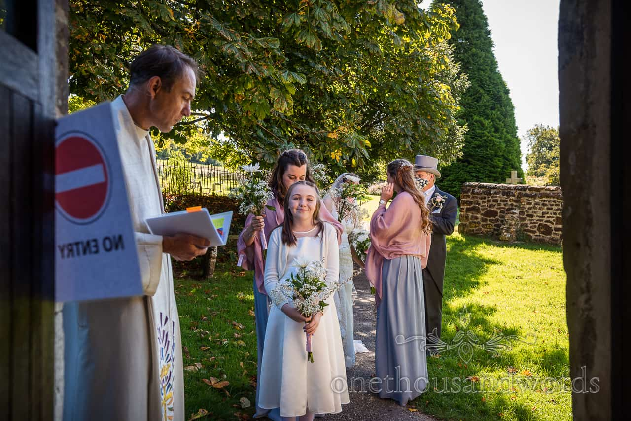 Flower girl and bridesmaids wait outside church door with no entry sign