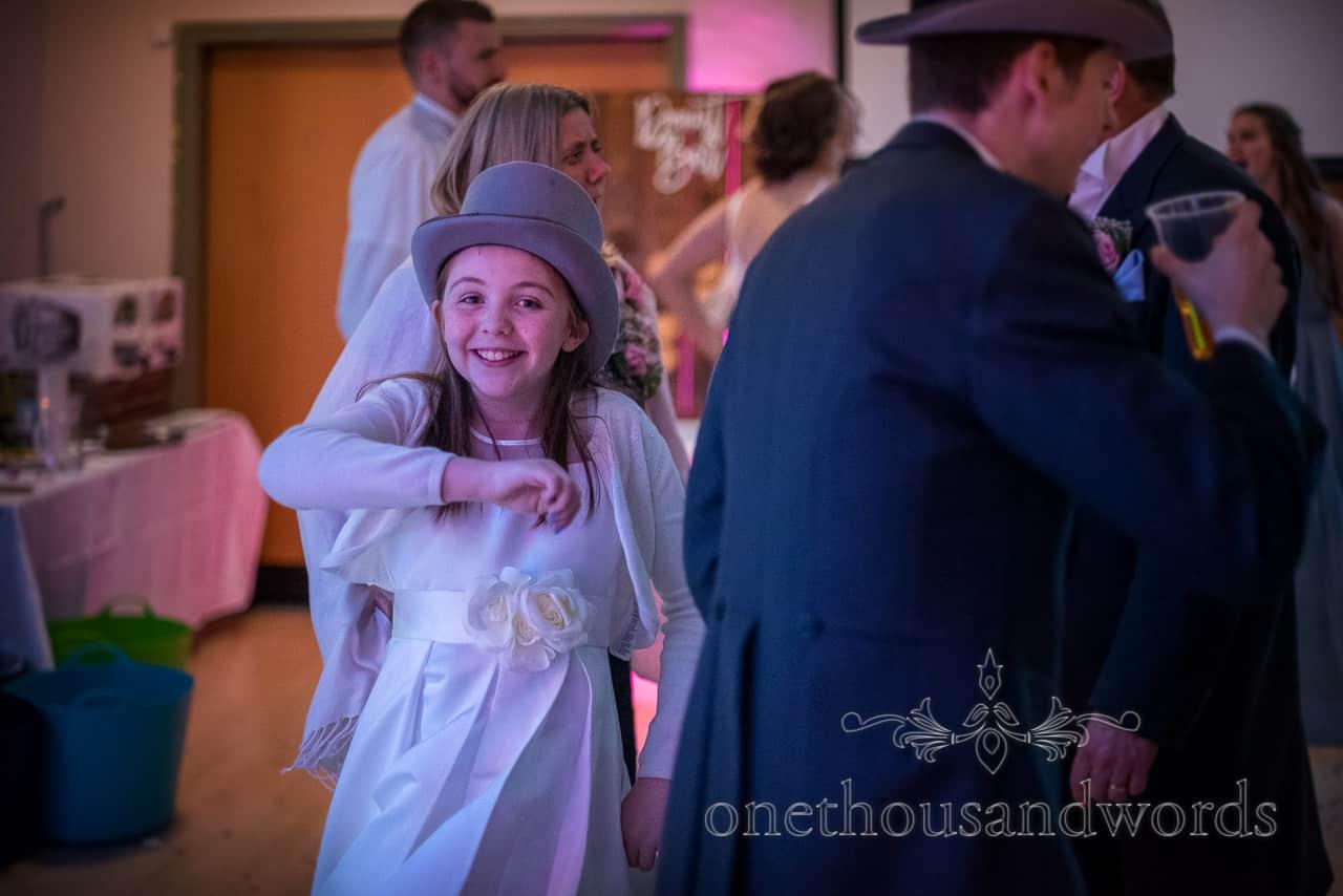 Flower girl dances at village hall wedding photographs of evening disco wearing top hat