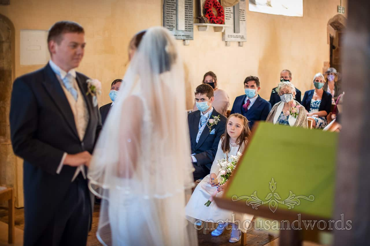 Flower girl and wedding guests wearing face masks watch marriage vows in church