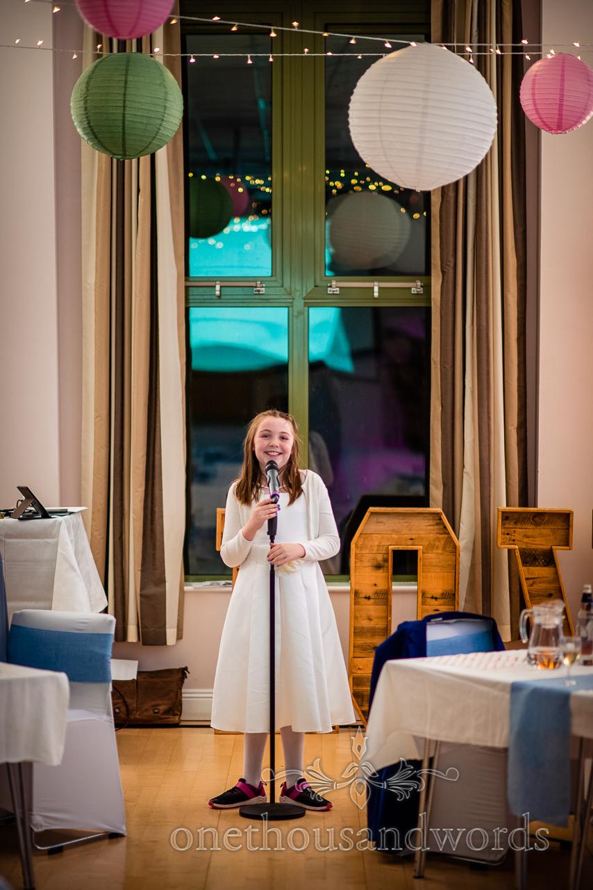 Flower girl in white dress tells jokes on Village Hall wedding photographs evening
