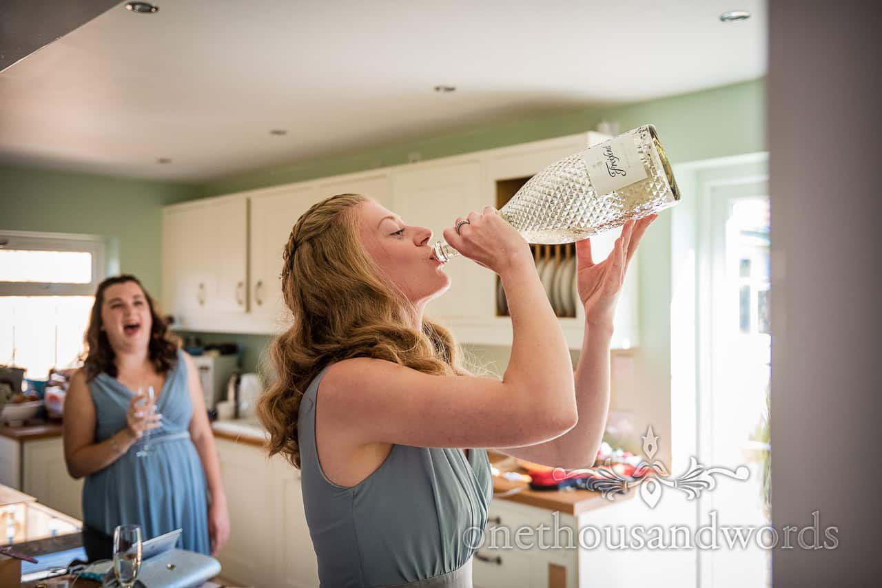 Funny bridesmaid in green dress drinking from huge champagne bottle