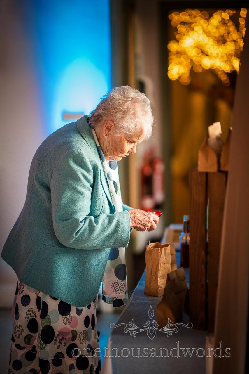 Grandmother in blue jacket at wedding sweet bar