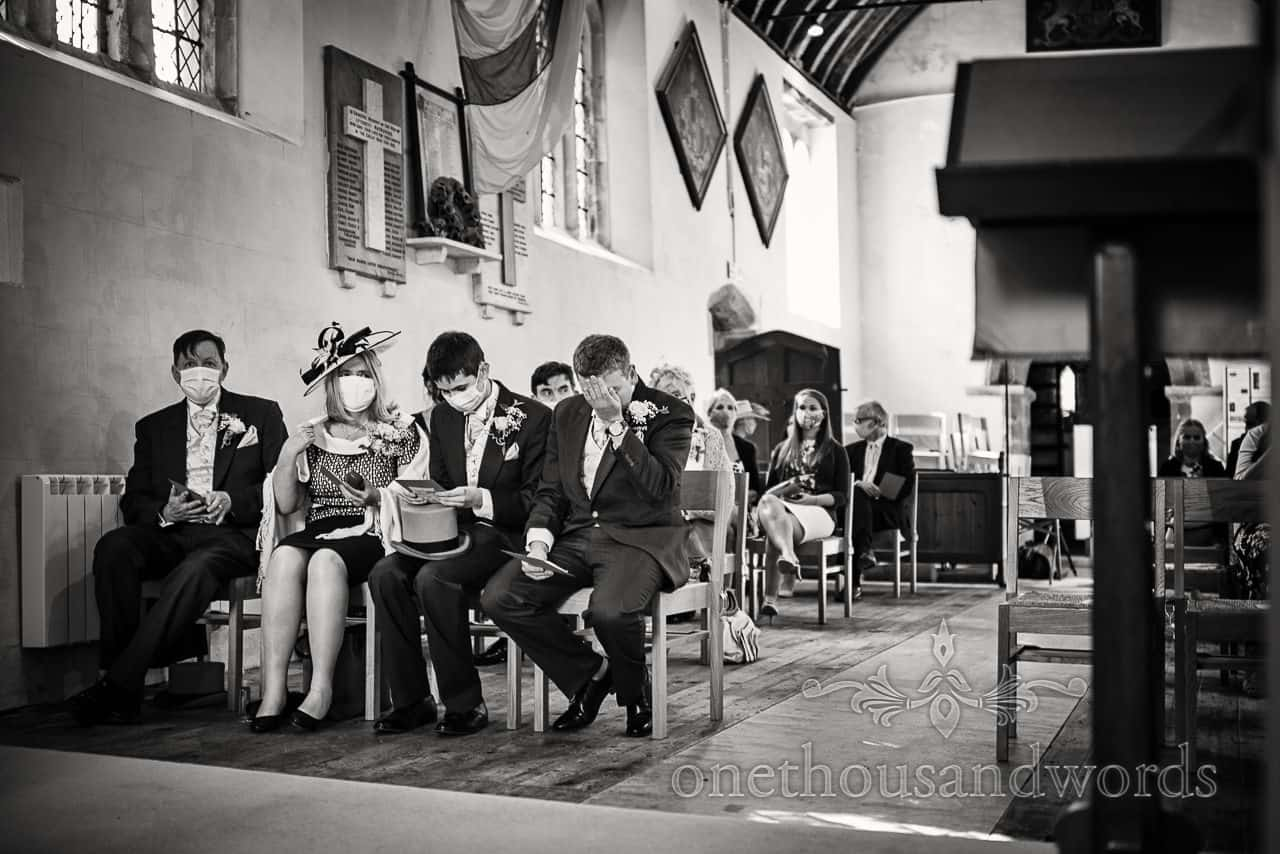Groom covering his face with hand during covid secure church wedding