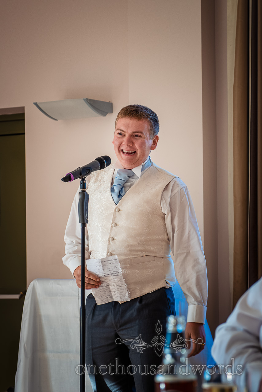 Laughing groom in white waistcoat gives wedding speech