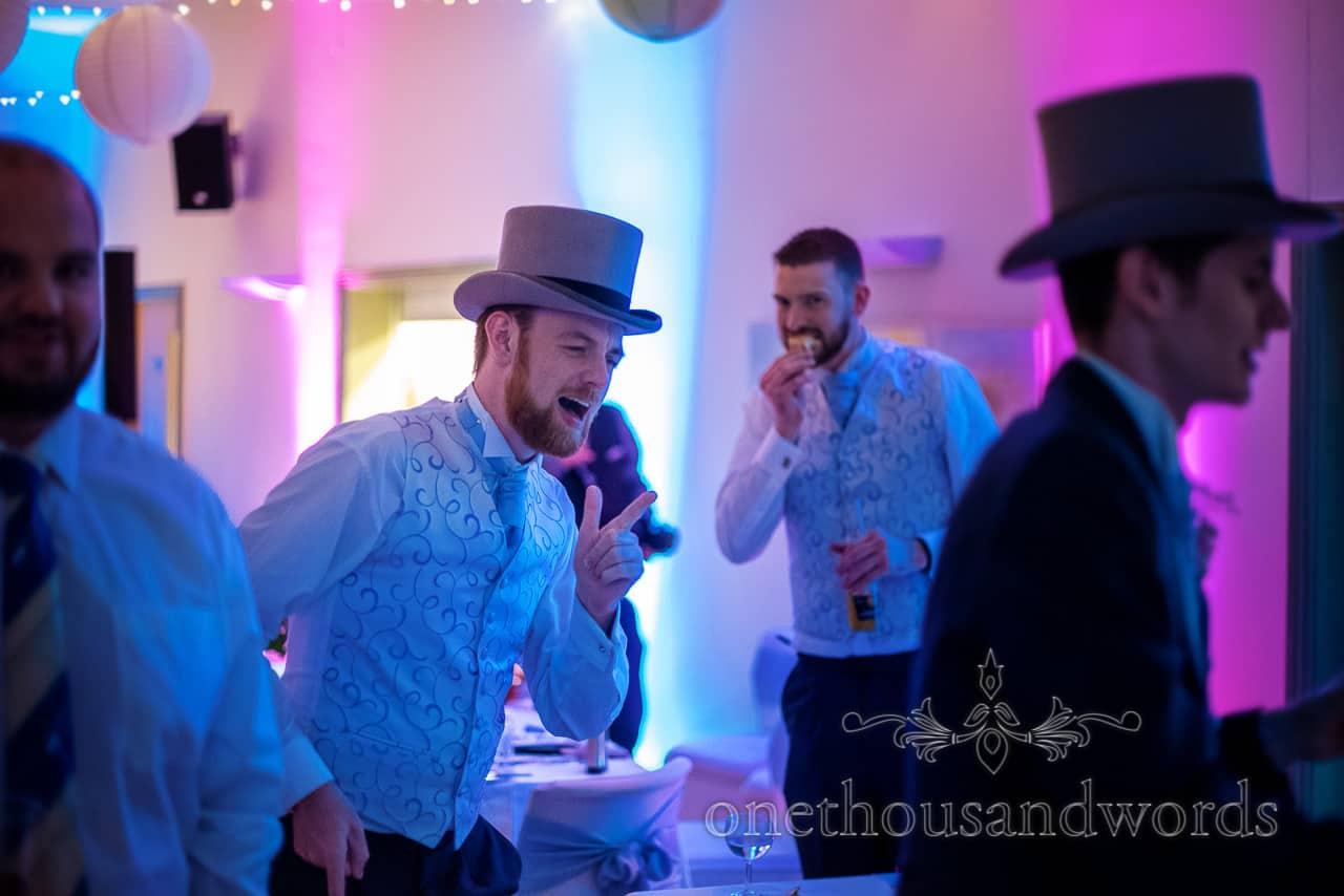 Groomsman in top hat dancing from village hall wedding photographs