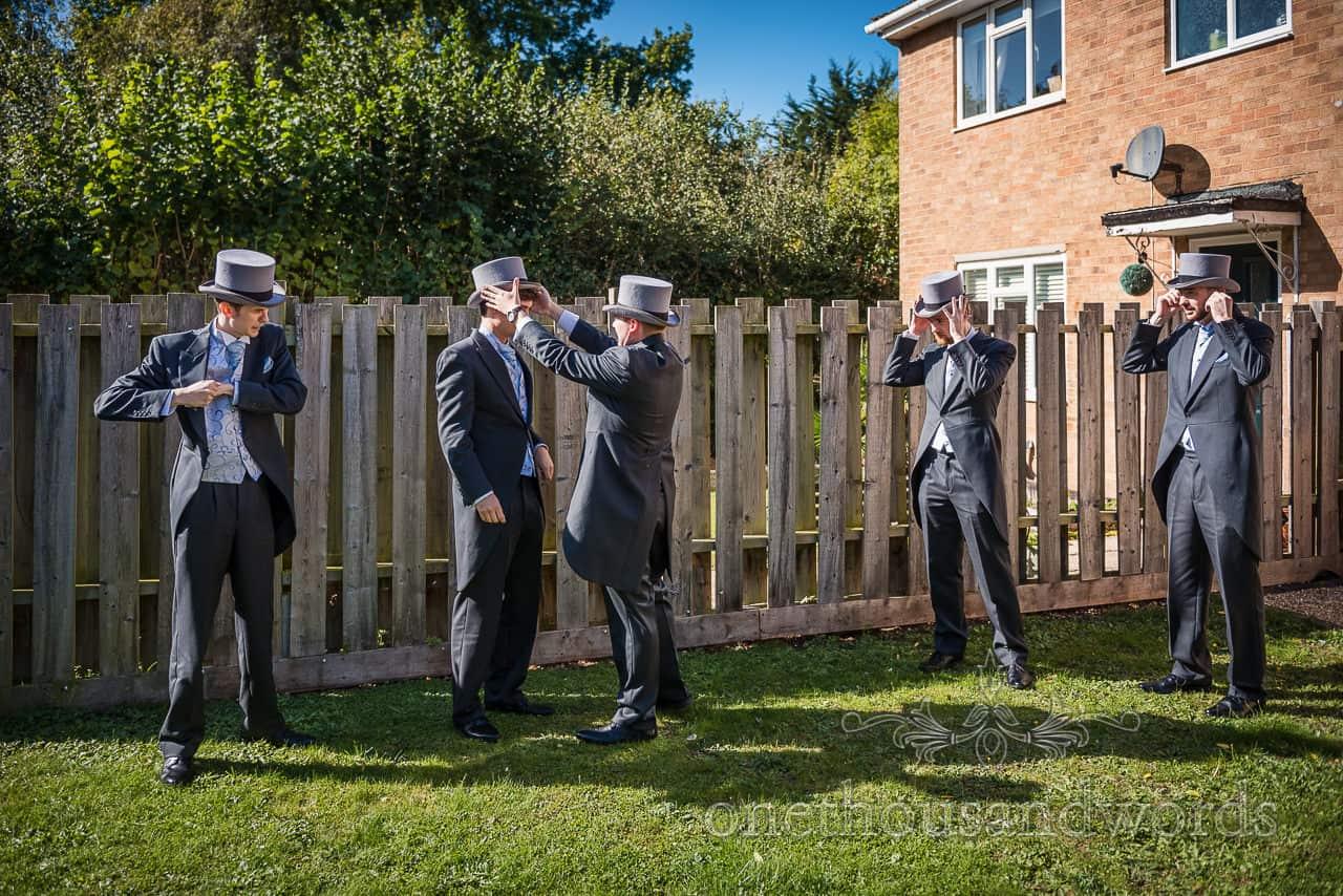 Groomsmen in random poses fit grey top hats in garden