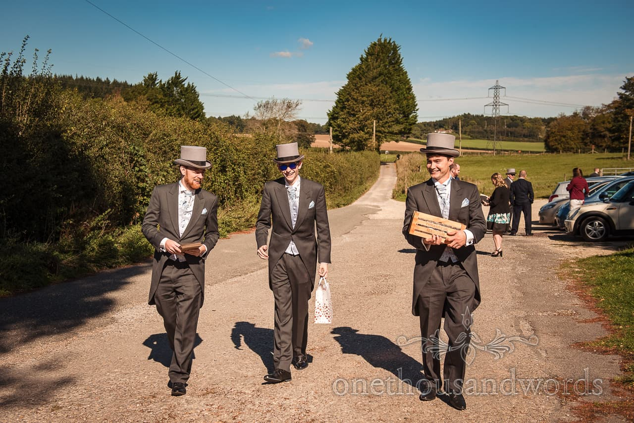 Groomsmen in grey top hats and tails walk towards church with orders of service and confetti