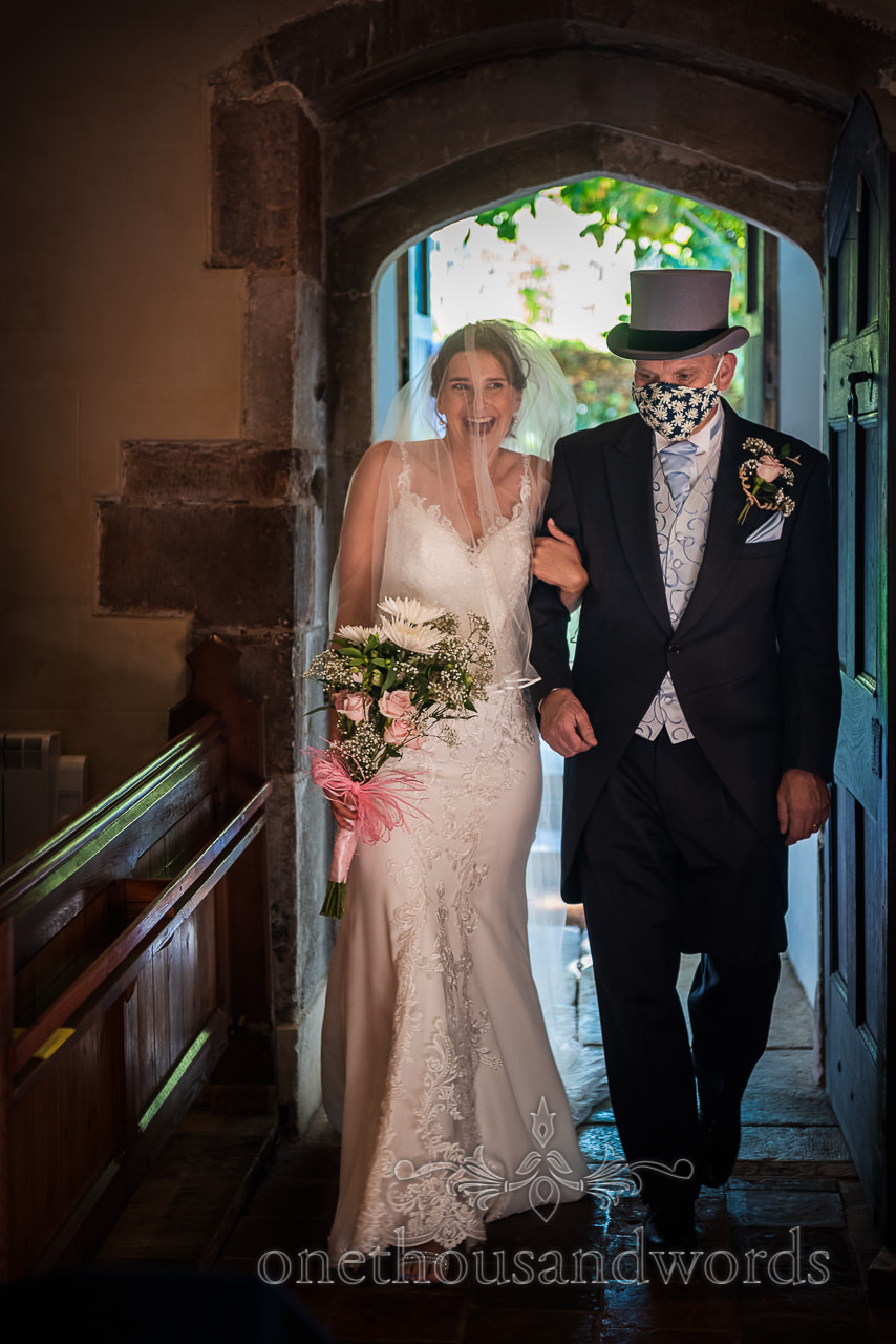 Happy bride enters church wedding ceremony with father in face mask and top hat