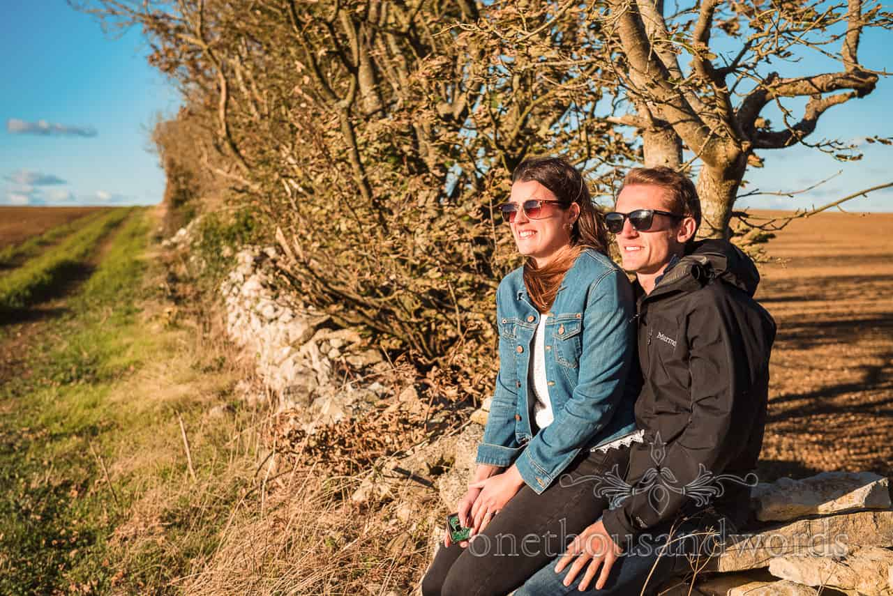 Happy couple sit on Dorset countryside dry stone wall