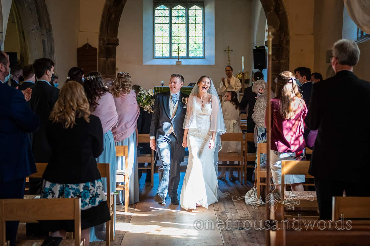 Laughing bride and groom walk down church aisle hand in hand