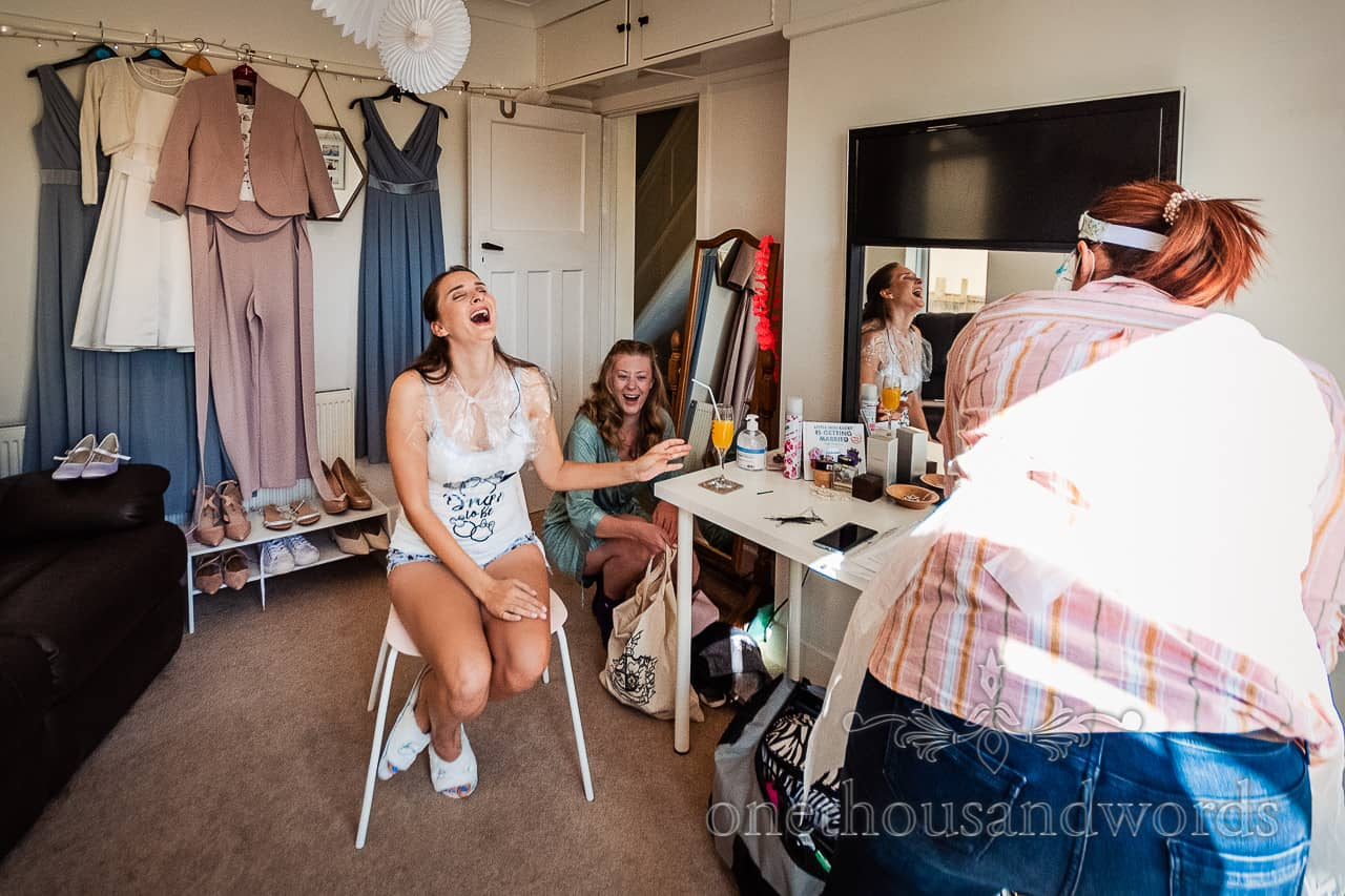 Laughing bride reaches for her drink in wedding morning preparation room