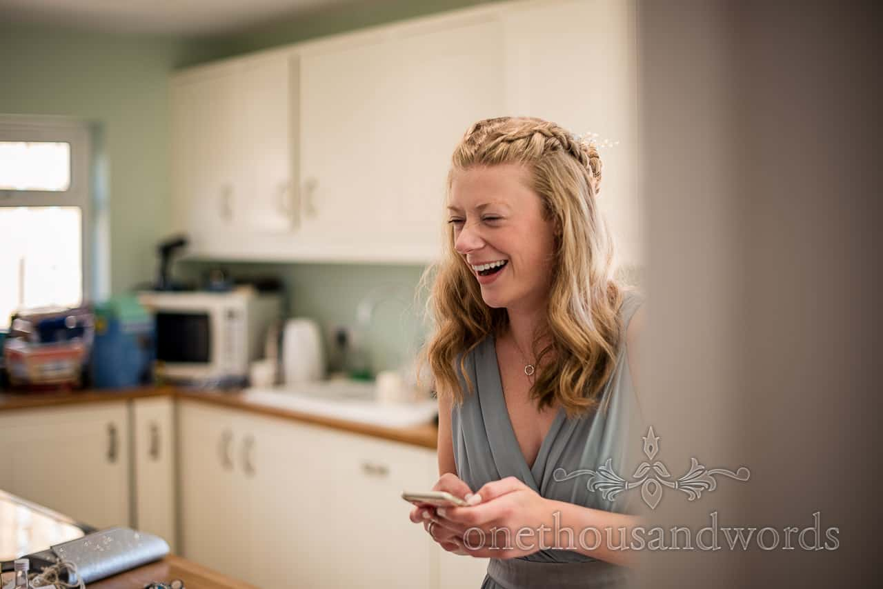Laughing bridesmaid in mint green dress laughing whilst texting on wedding morning