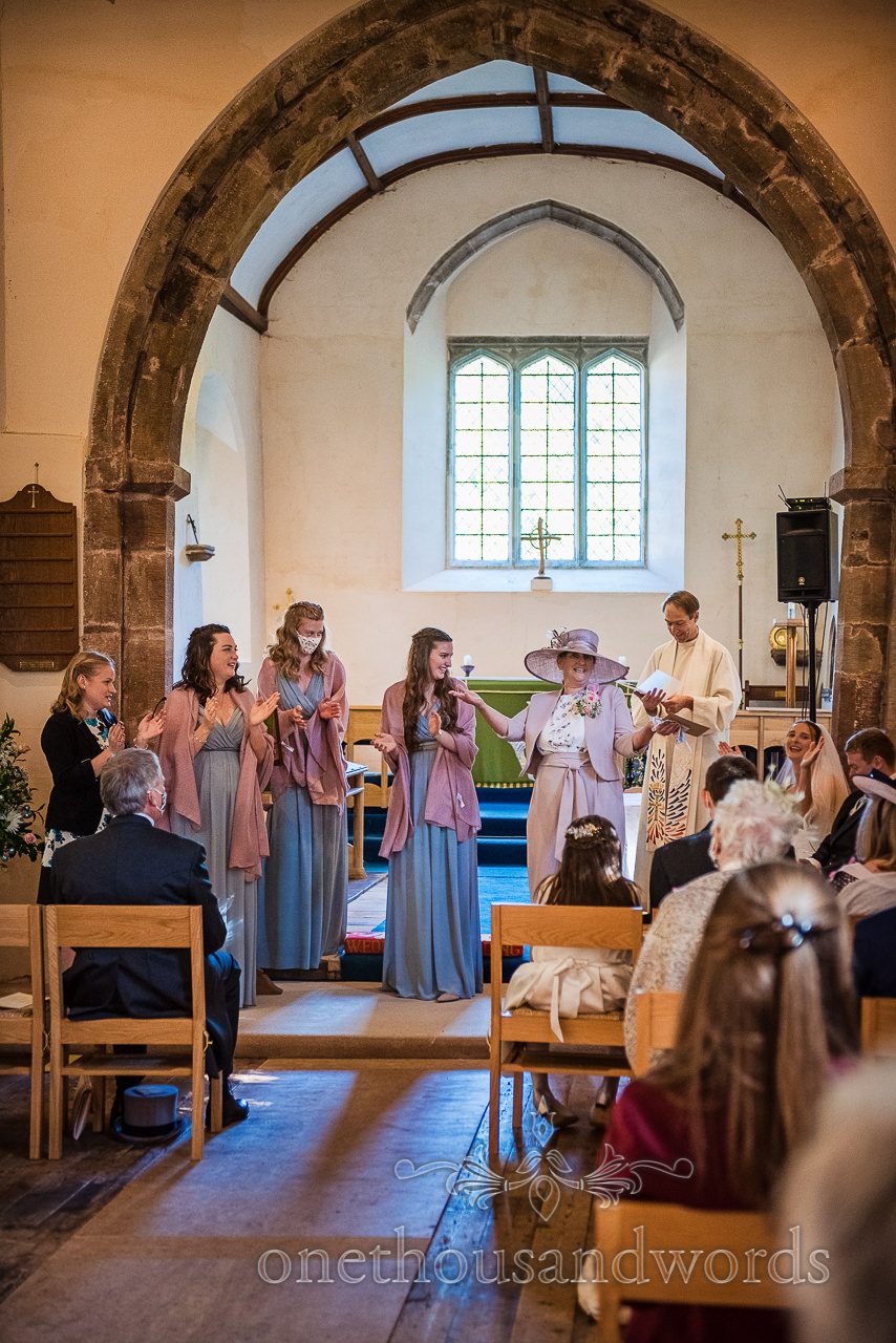 Mother of the bride and bridesmaids perform clapping poem at church wedding ceremony