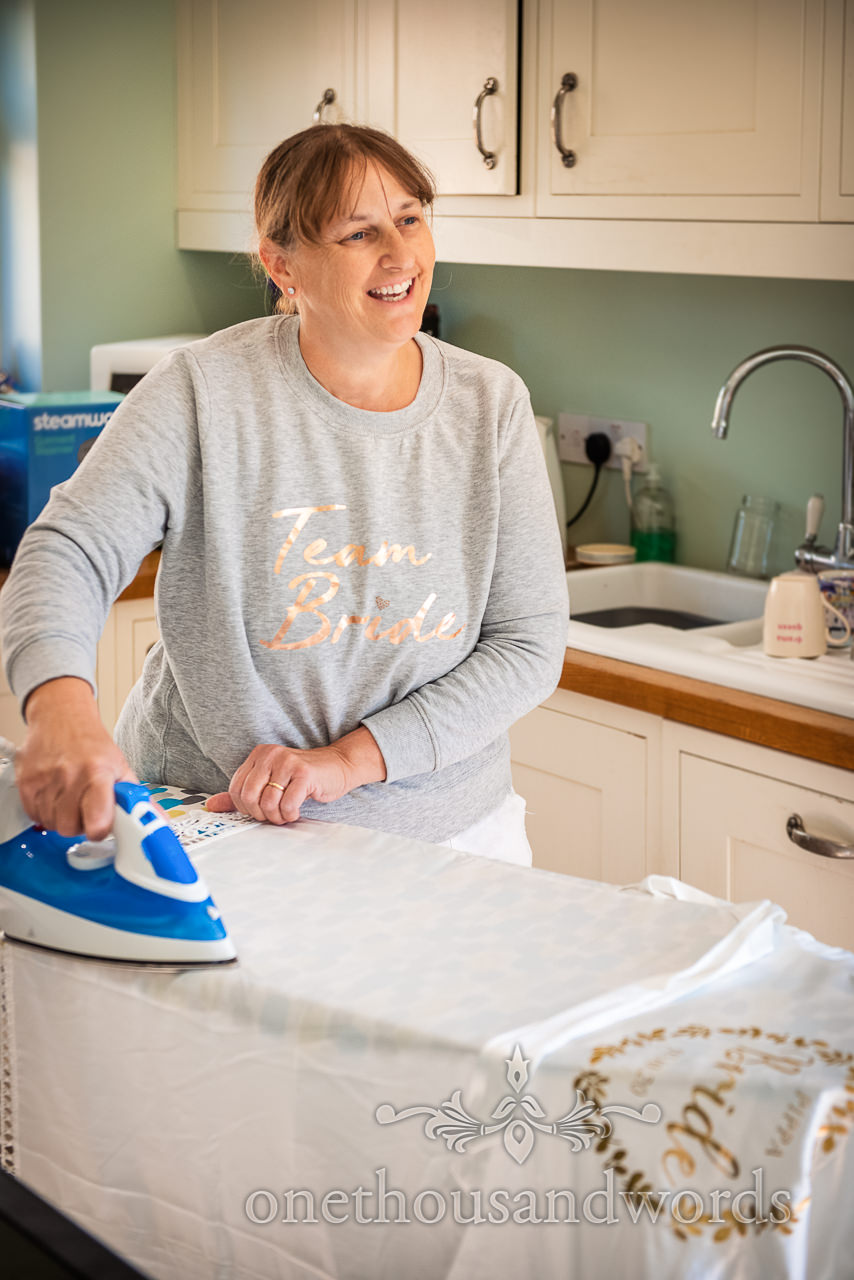 Mother of the bride ironing custom dressing gown on wedding morning