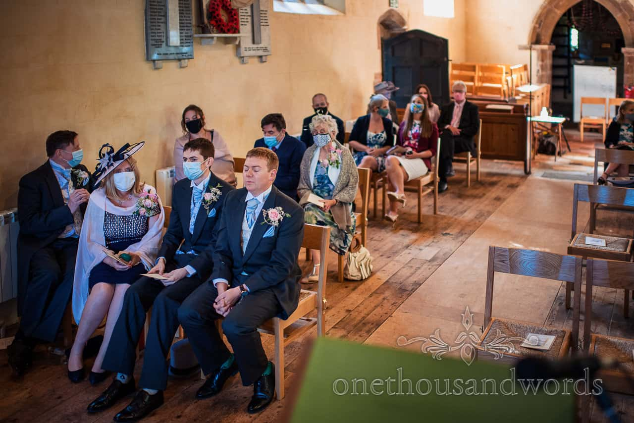 Newrvous looking groom shuts his eyes and takes deep breaths at covid secure church wedding