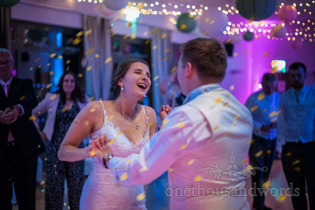 Village hall wedding photographs of first dance under gold confetti
