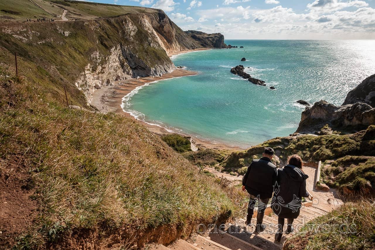 Couple walk hand in hand down steps to Man'O War beach in Dorset