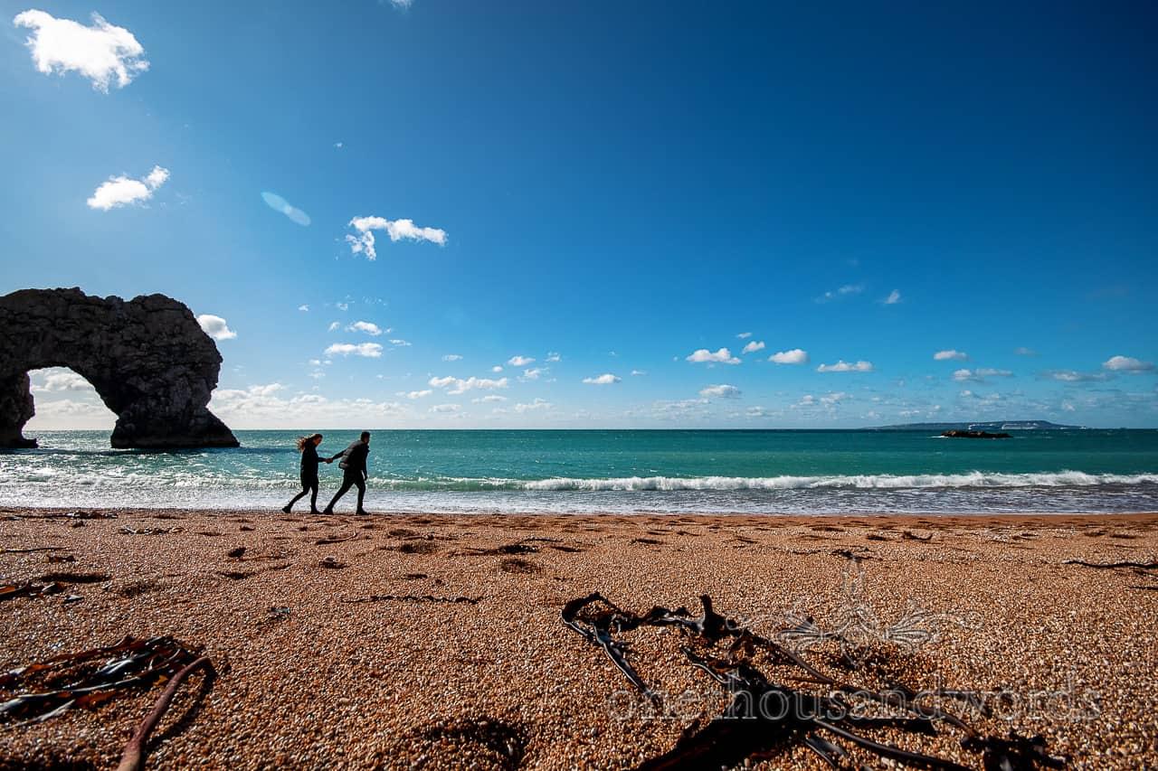 Proposal photo shoot couple walk along Durdledoor beach in Dorset