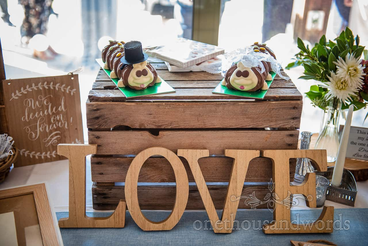 Rustic wooden love sign against crate with two caterpillar wedding cakes