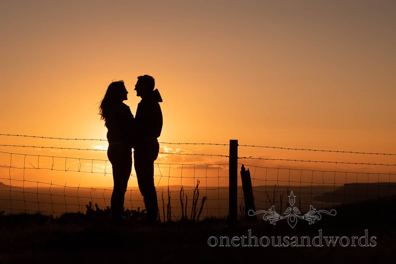 Silhouette of an engagement photo shoot couple at sunset