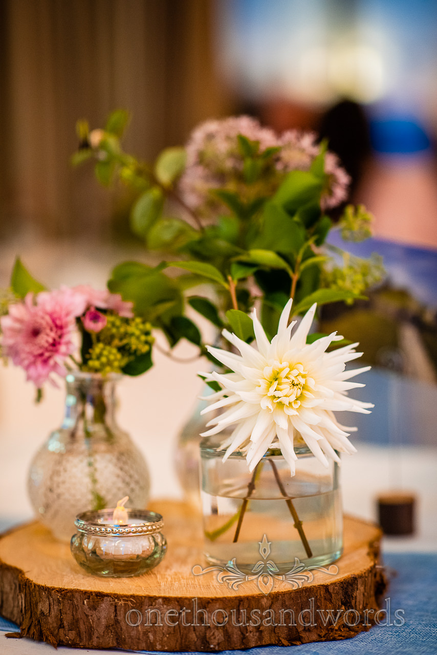 Village hall wedding photographs flowers center piece in glass jars on wooden slice