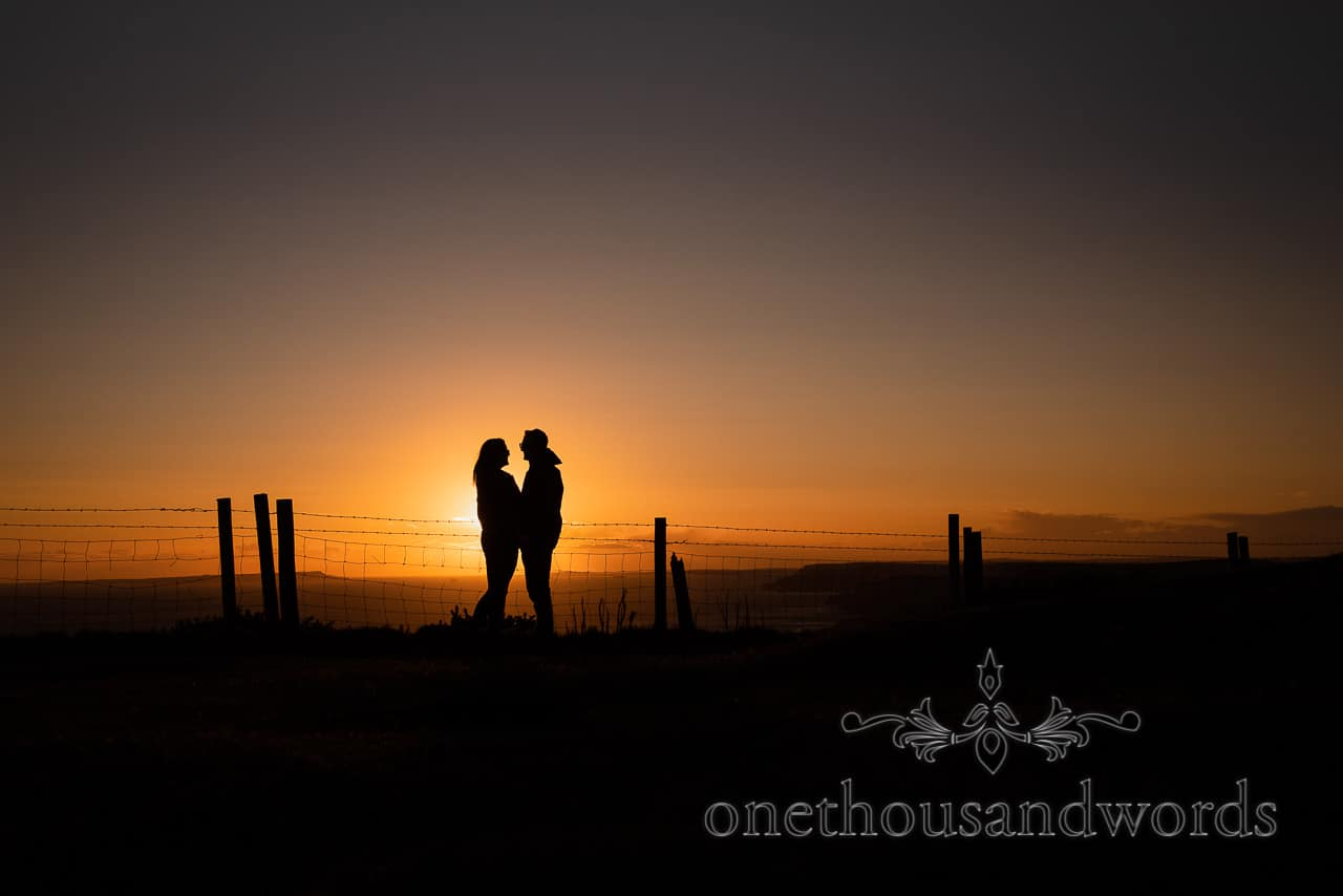 Sunset over the sea Swyre Head engagement photographs of silhouetted couple