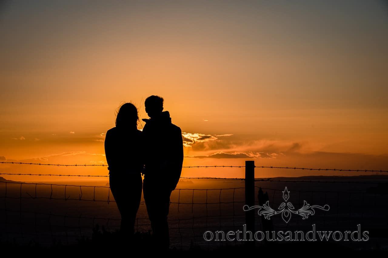 Sunset silhouetted couple on Dorset coast