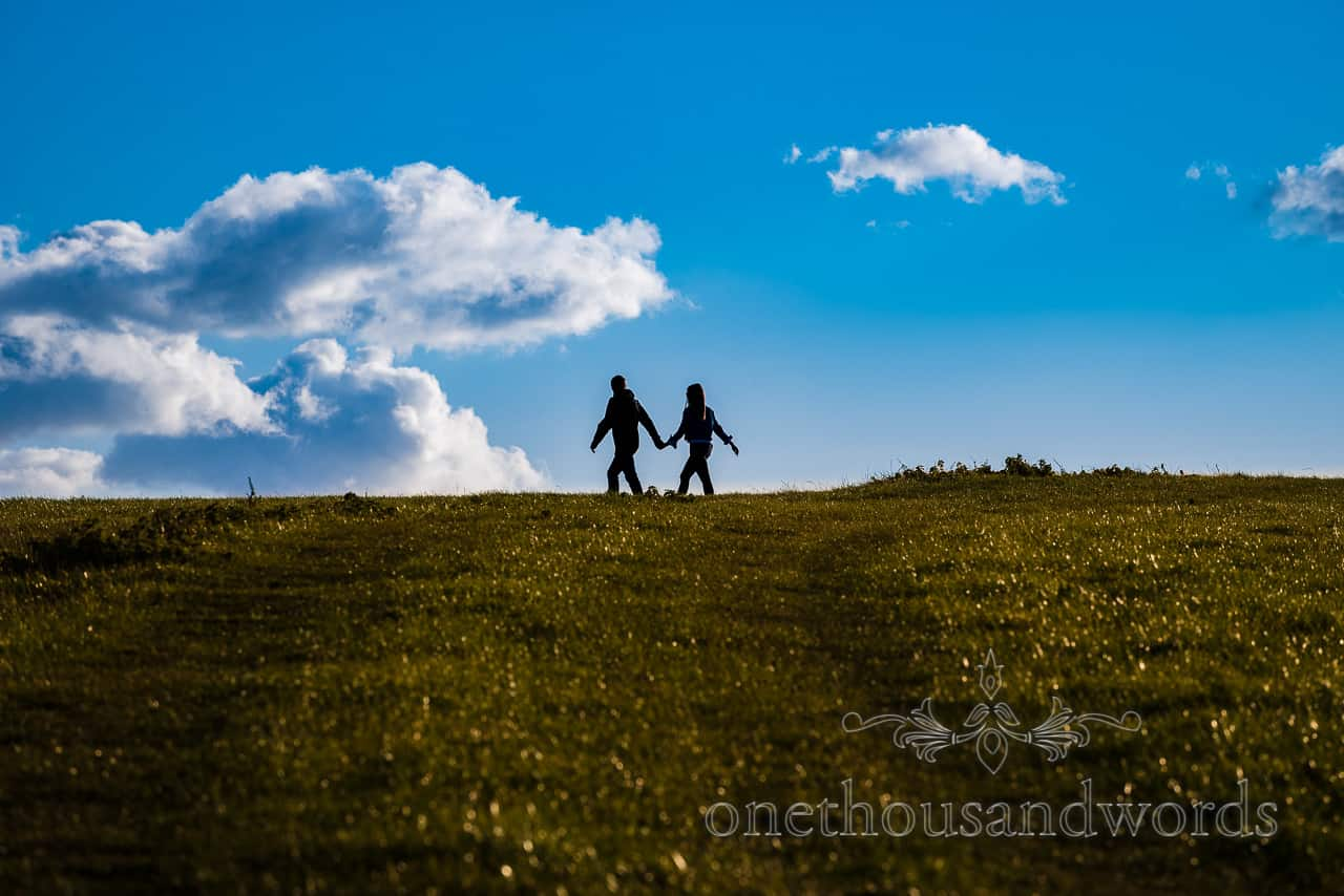Engagement photo shoot of couple in silhouette against blue sky