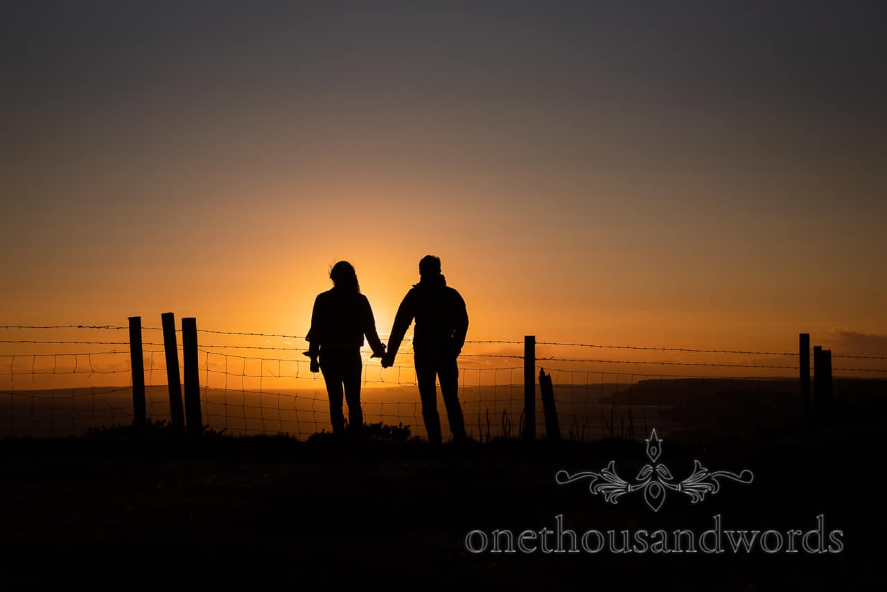 Swyre Head engagement photographs of couple in silhouette holing hands at sunset