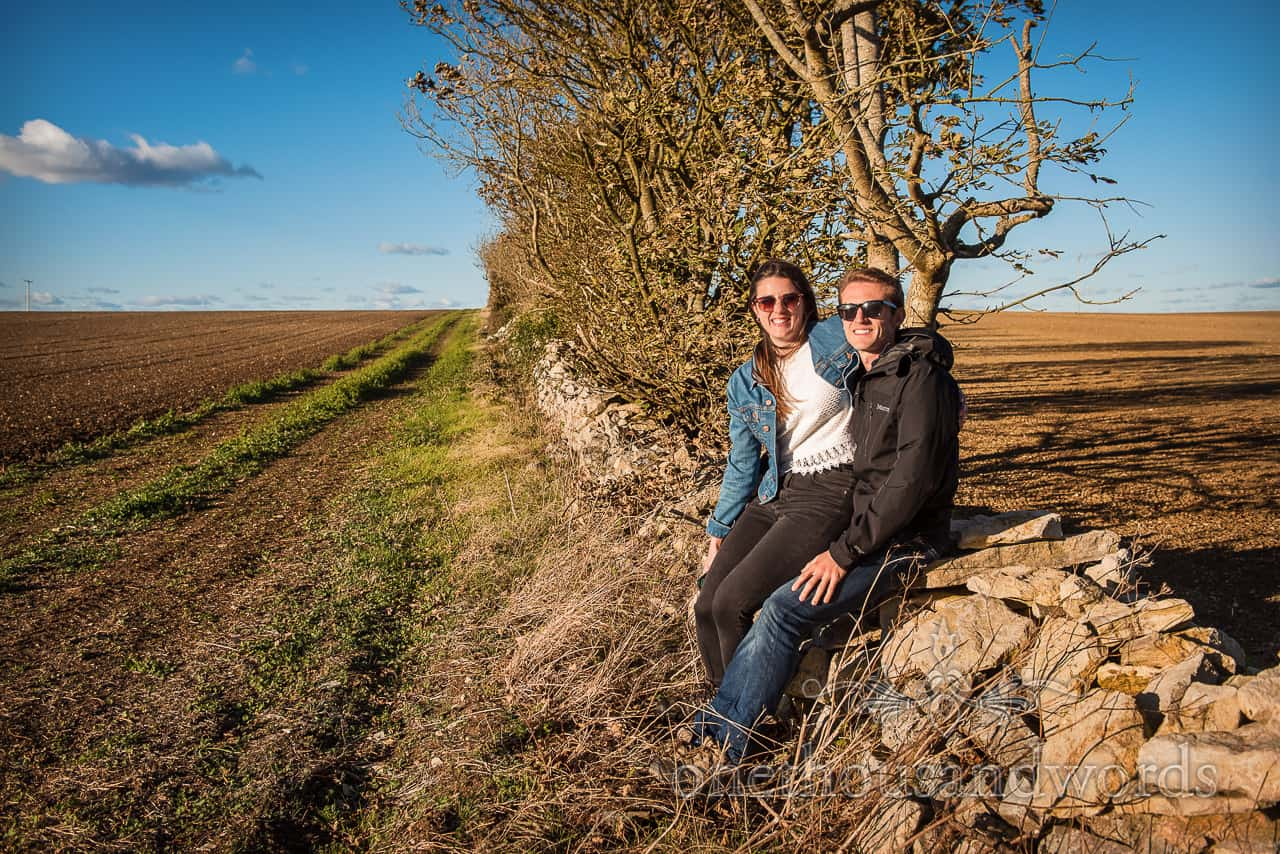 Happy engagement shoot couple sitting on Purbeck dry stone wall