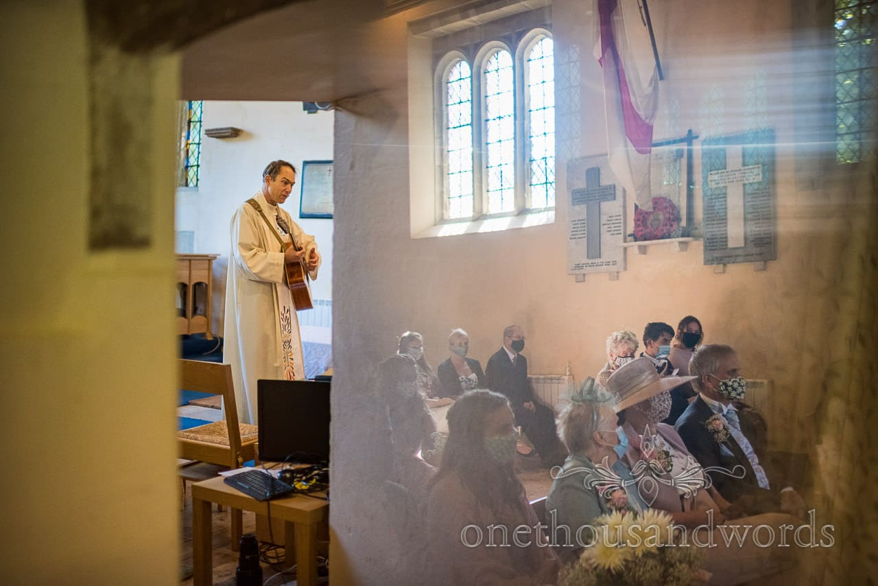 Vicar plays the guitar to wedding guests wearing face masks during COVID secure wedding