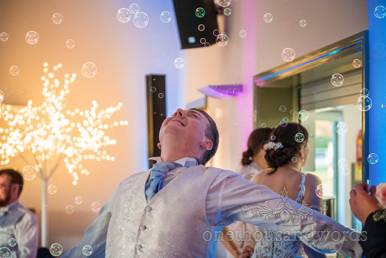 Village Hall wedding with groom dancing in cloud of bubbles