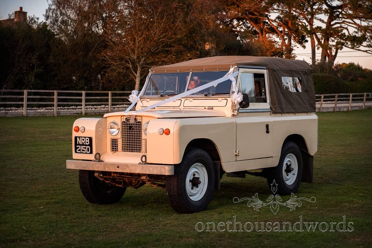 vintage cream Landrover classic wedding car at sunset from Dorset village hall wedding photographs