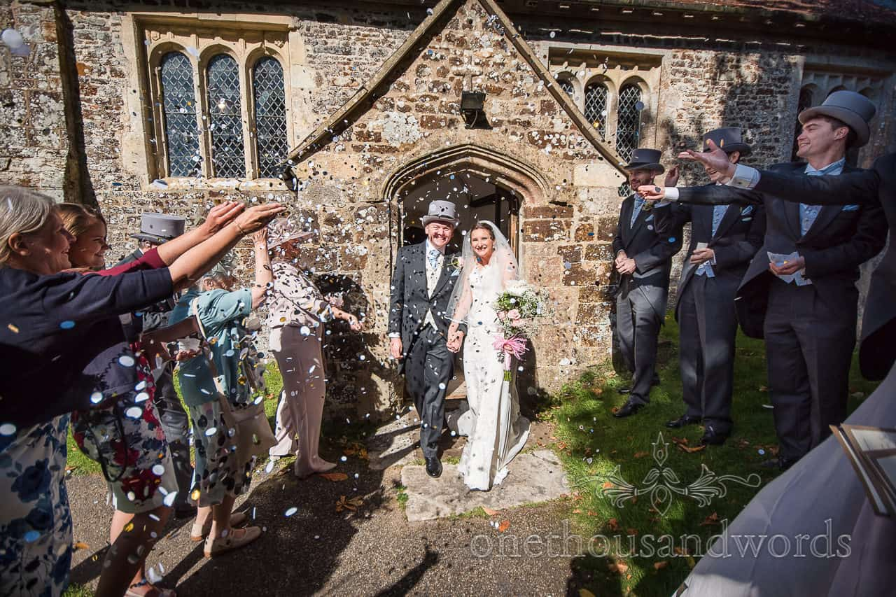 Wedding confetti is thrown outside stone village church