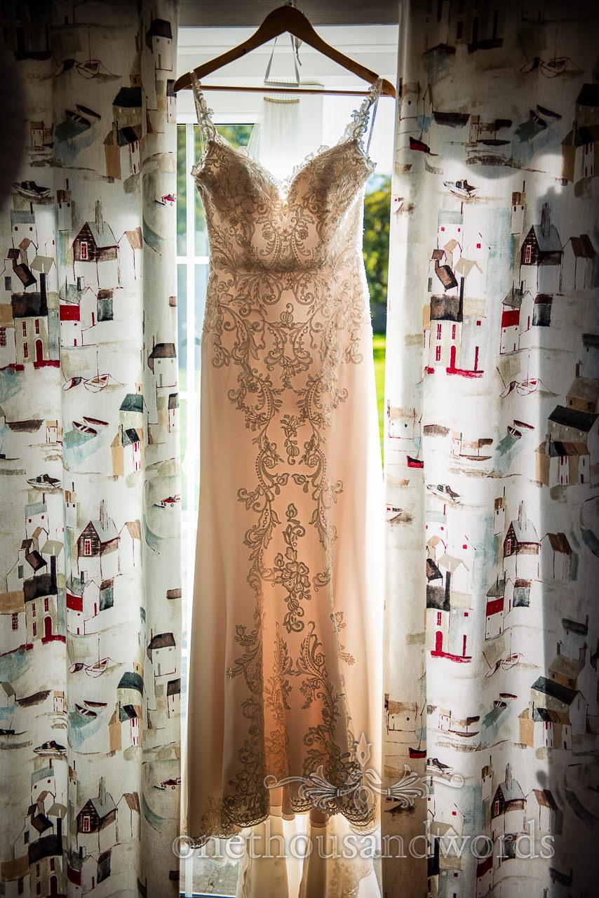 Detailed wedding dress hangs between curtains glowing in window light
