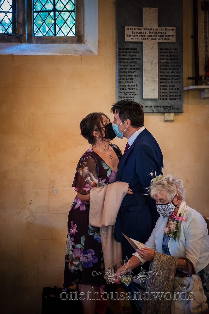Wedding guests in church kiss through COVID face masks