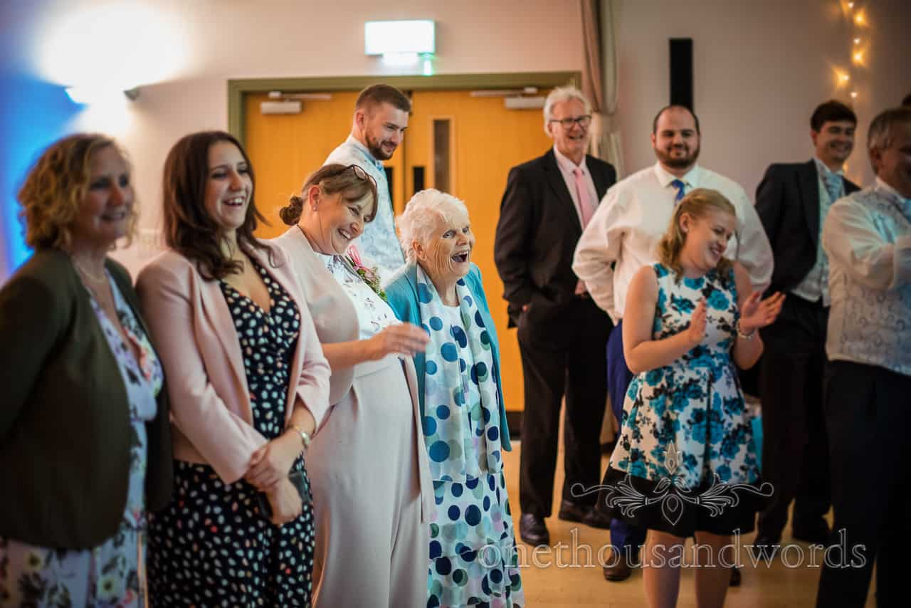 Wedding guests laughing at bride and groom cutting the cake