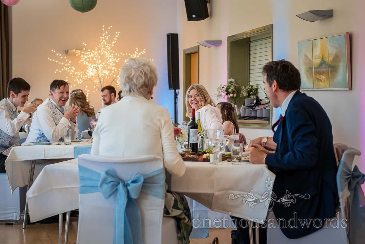 Seated wedding guests laughing at Village Hall wedding photographs of breakfast